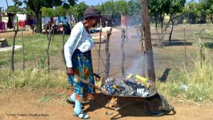 Centenarian Lucy Mahlangu lives with her 4-year-old granddaughter. Here, she moves burning rubbish away from her Stinkwater home