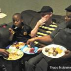 Zanele Malambe (far right) and her 9-year-old son Tshepo sit down to a Sunday dinner of pap, potato salad, pumpkin, beetroot, and a tinned fish and macaroni salad.