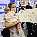 New mother Dr Dalene von Delft joins the Treatment Action Campaign in storming the stand of French multinational pharmaceutical company Sanofi. Delft, a multidrug-resistant tuberculosis (TB) survivor, holds a placard demanding the company ensures adequate supplies of its childhood TB vaccine are available worldwide.
