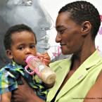 Monique and Jaden Davids stand in front of a mural of themselves being painted at the World Lung Health Conference. Jaden developed TB at two months old.