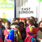 Neno and Raya of Takalani Sesame celebrating the launch of new educational resources with Hope School children at Johnson & Johnson in East London.