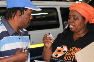 Nonhlanhla Skosana, from Sonke Gender Justice, speaks to a taxi driver about the Safe Ride campaign. Credit: Amy Green