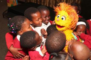 Learners from Shad Mashologu Junior Primary School playing with a muppet from Takalani Sesame TV show