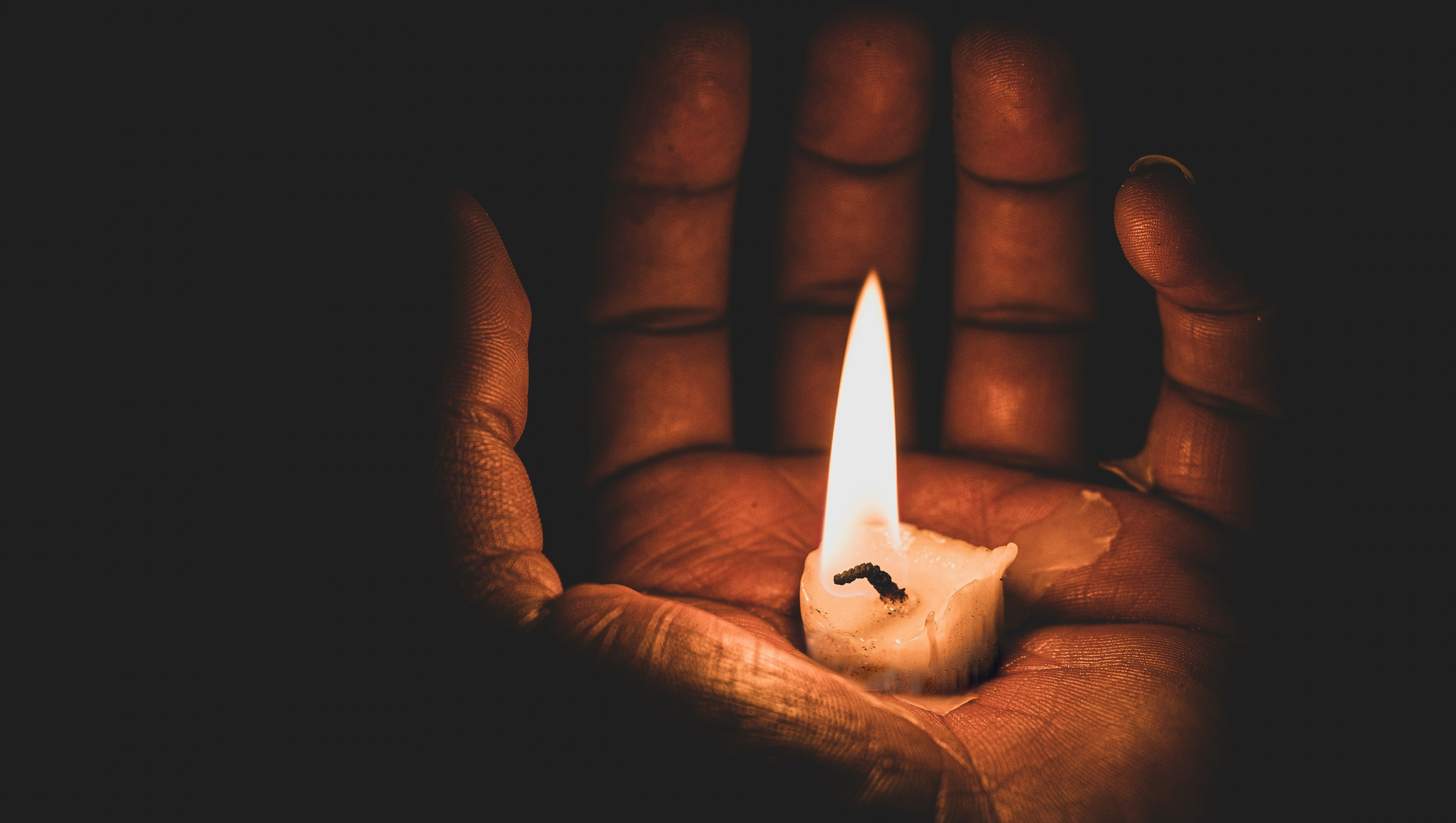 A hand holding a candle symbolising the dead