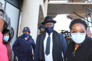 Police Minister Bheki Cele with a mask being escorted by acting Health Minister