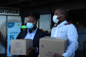 Two police officers carrying boxes and wearing masks
